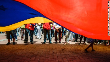 TOPSHOT - Opposition activists and members of the National Orchestra System hold a demonstration in rejection of the recent deaths of young people by security forces -within opposition protests- in Caracas on May 7, 2017. The last death in Venezuela's unrest, of a 22-year-old man, occurred during looting in Valencia, one of Venezuelan cities hardest hit by a worsening economic crisis. Demonstrators blame Maduro for the country's plight and the shortages of food and medicine, and demand elections to remove the leftist president.  / AFP PHOTO / JUAN BARRETO        (Photo credit should read JUAN BARRETO/AFP/Getty Images)