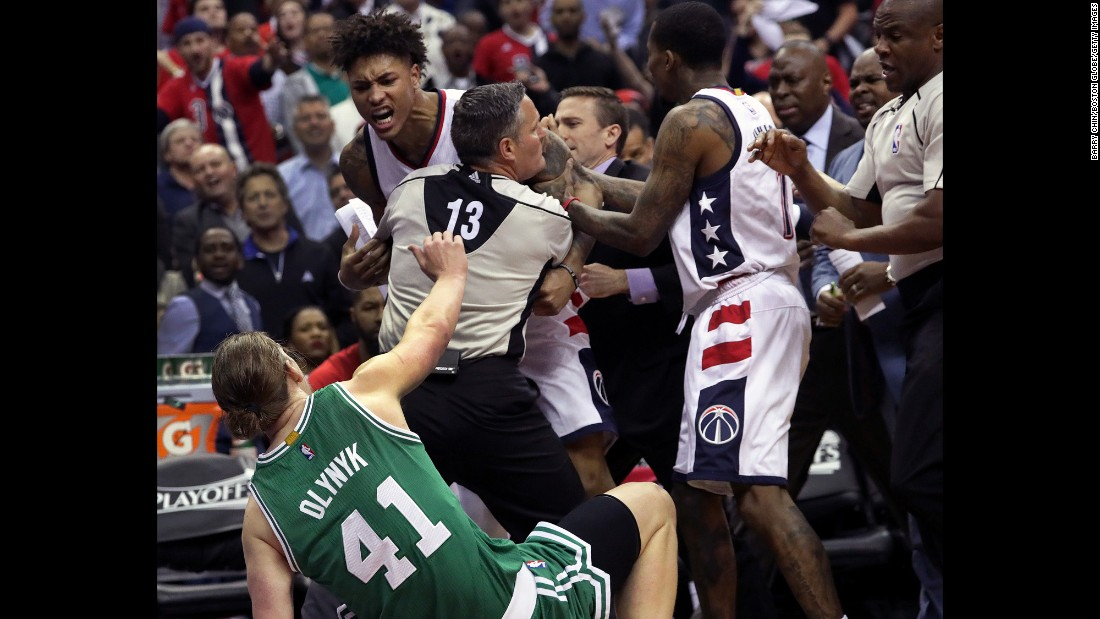 An official holds back Washington's Kelly Oubre after Oubre used his forearm to knock down Boston center Kelly Olynyk on Thursday, May 4. Oubre was ejected from the playoff game and suspended for the next one.