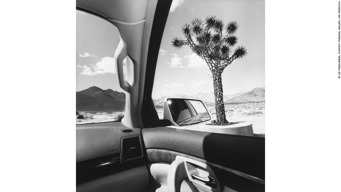 """When planning 'Autophoto,' we were not only interested in how the car provided a subject and new set of themes for photographers, but also in how it offered them a new way of exploring the world and a new means of expression. The photographs from <a href=""https://fraenkelgallery.com/artists/lee-friedlander"" target=""_blank"">Lee Freidlander</a>'s 'America by Car' series illustrate this idea perfectly. He took the photographs for this series on various road trips, over a 15-year period, looking to capture the eccentricities of the American roadside. In these photographs, the different elements inside of the car, for example the steering wheel, rear-view mirrors and windows, provide the photographer with a variety of compositional devices, allowing him to create a humorous view of America's distinctive visual landscape."""