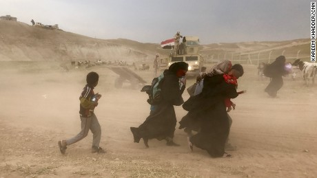 Residents from northwest Mosul flee fighting between Iraqi security forces and ISIS during a sandstorm carrying few belongings and their children in their arms.