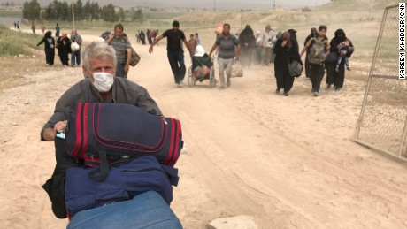 Resident from northwest Mosul pushes his belongings on a stroller as he flees fighting there.