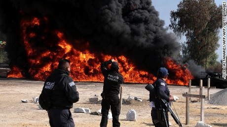 State policemen take pictures following the explosion of a petrol pipeline caused by fuel theft, in Acatzingo, Puebla State, on March 7, 2017.  / AFP PHOTO / JOSE CASTAÑARES        (Photo credit should read JOSE CASTANARES/AFP/Getty Images)