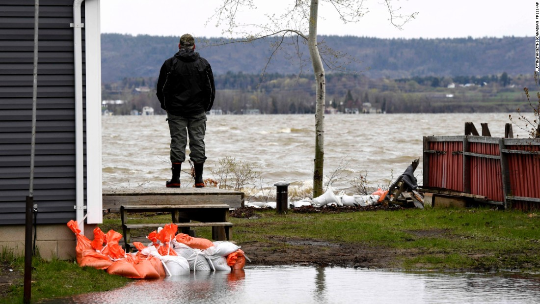 Steve Tousignant watches the Ottawa River from the deck of his home in Constance Bay, an Ottawa neighborhood, on Monday, May 8. Torrential rains and melting snow have caused flooding in various parts of Canada.