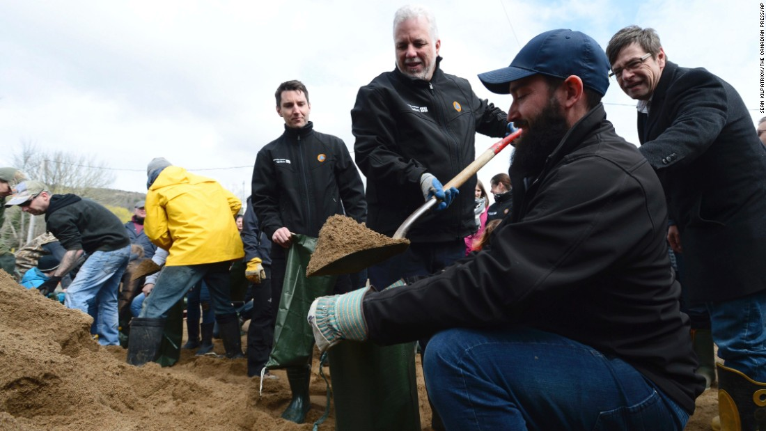 Quebec Premier Philippe Couillard uses a shovel to fill a sandbag as he tours a flood-affected area in Luskville, Quebec, on May 8.