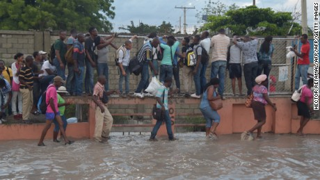 A group of people walk in a partially flooded street by the rains, while another persons try to walk over the water, holding themself in a grating, in the Haitian capital Port-au-Prince, on May 2, 2017. / AFP PHOTO / HECTOR RETAMAL        (Photo credit should read HECTOR RETAMAL/AFP/Getty Images)