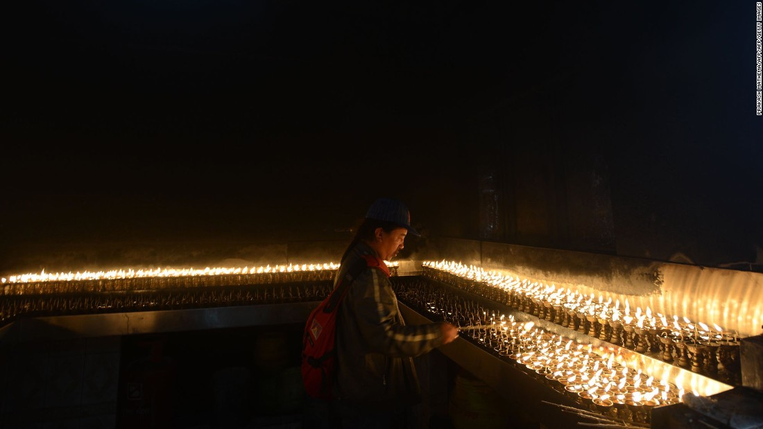 <strong>Nepal: </strong>A Nepalese Buddhist devotee lights oil lamps at a temple in Kathmandu. Buddha was born in Lumbini, Nepal some 125 miles southwest of the Kathmandu valley.