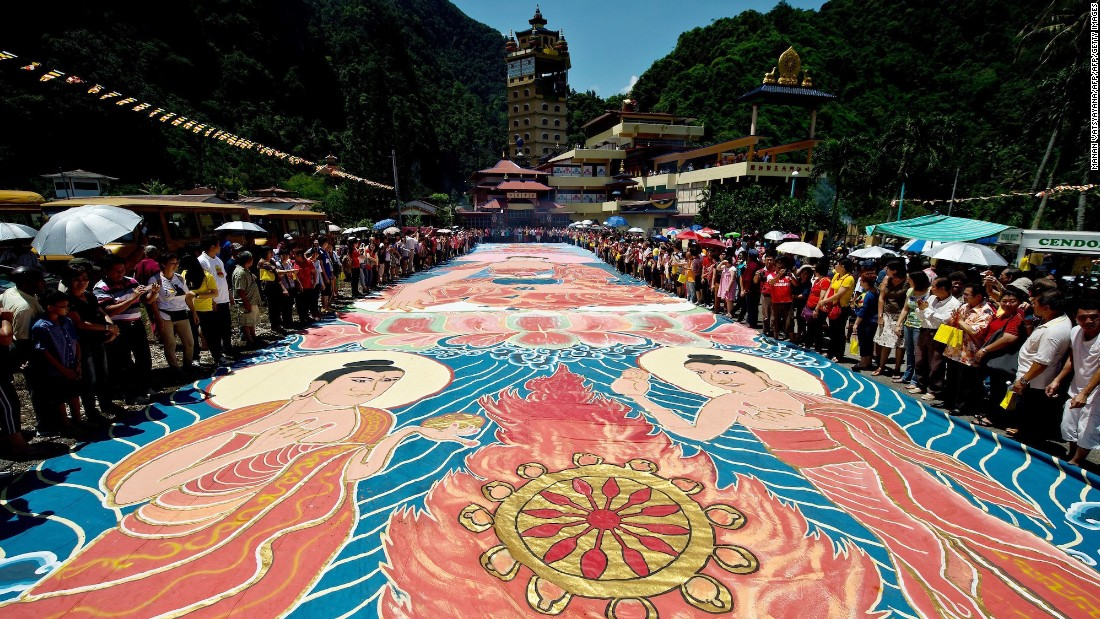 "<strong>Ipoh, Malaysia: </strong>Buddhist devotees unfurl a 196-foot-long sacred ""Thangka"" under the sun during Vesak Day celebrations at Ipoh's Enlightened Heart Tibetan Buddhist temple. Every year, hundreds of devotees take part in this 'Sunning Buddha ritual.' According to traditional beliefs, sunning the Thangka will allow it to absorb the powers of the sun and promote peace, harmony, success and good health for the rest of the year."