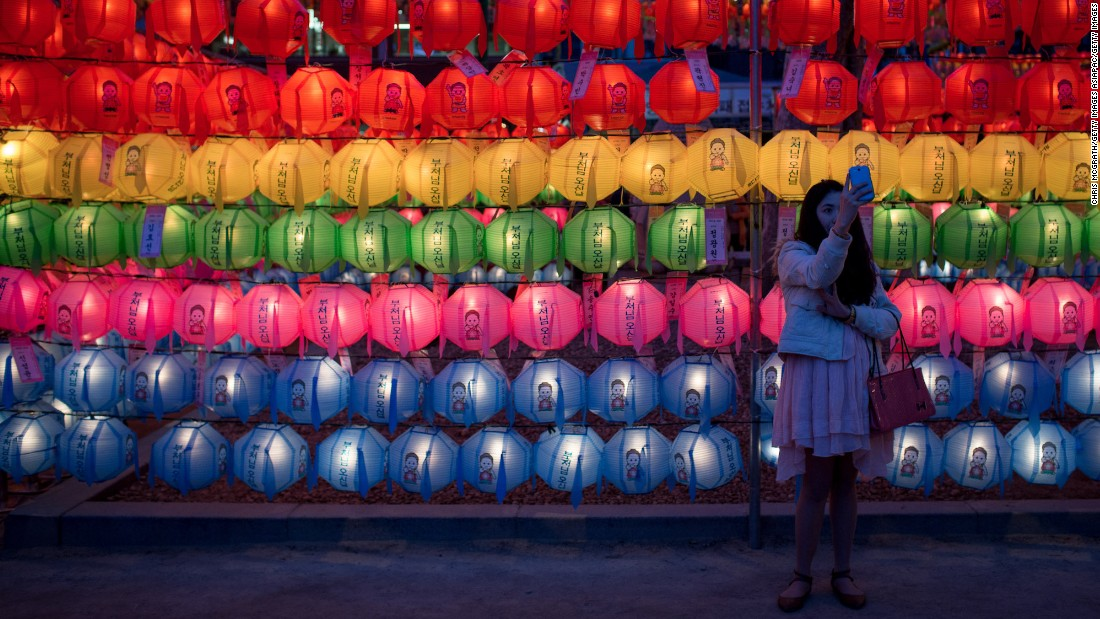 <strong>Seoul, South Korea: </strong>A woman takes a selfie in front of lines of lit lanterns during a past Vesak Day festival at Seoul's Jogyesa Temple, a popular site for Buddhists celebrating Buddha's birthday.