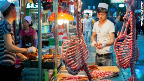 An ethnic Hui butcher carves lamb meat at the Muslim quarter in Xi'an.
