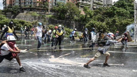 "Opposition activists use a mega-catapult against riot police during a protest against President Nicolas Maduro in Caracas, on May 10, 2017. Venezuelan protesters hit the streets on Wednesday armed with ""Poopootov cocktails,"" jars filled with excrement which they vowed to hurl at police as a wave of anti-government demonstrations turned dirty. / AFP PHOTO / JUAN BARRETO        (Photo credit should read JUAN BARRETO/AFP/Getty Images)"