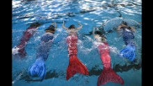 Women practice swimming with mermaid tails at AquaMermaid swimming school in Chicago. Fitness experts believe any class engaging people in long-lost passions or curiosities will benefit the health of a population.