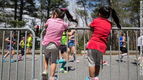 "WELLESLEY, MA - APRIL 17: Kids climb the barrier to watch the Boston Marathon runners in the iconic ""scream tunnel"" near Wellesley College on April 17, 2017, in Wellesley Massachusetts. (Photo by Kayana Szymczak/Getty Images)"
