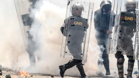 "National Guard personnel in riot gear charge on demonstrators during a protest against President Nicolas Maduro in Caracas, on May 10, 2017. Venezuelan protesters hit the streets on Wednesday armed with ""Poopootov cocktails,"" jars filled with excrement which they vowed to hurl at police as a wave of anti-government demonstrations turned dirty. / AFP PHOTO / JUAN BARRETO        (Photo credit should read JUAN BARRETO/AFP/Getty Images)"