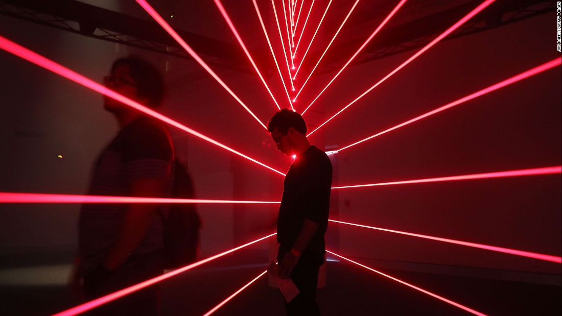 A man visits a laser exhibit at the Phillip and Patricia Frost Museum of Science, which opened Monday, May 8, in Miami.