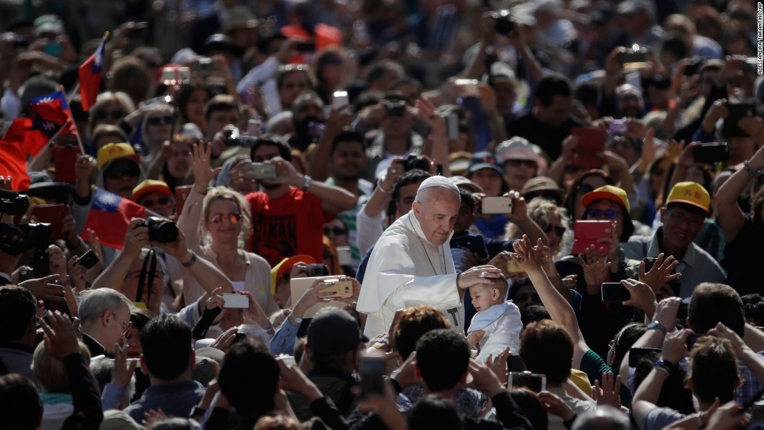 Pope Francis caresses a child's head Wednesday, May 10, as he arrives in St. Peter's Square at the Vatican.