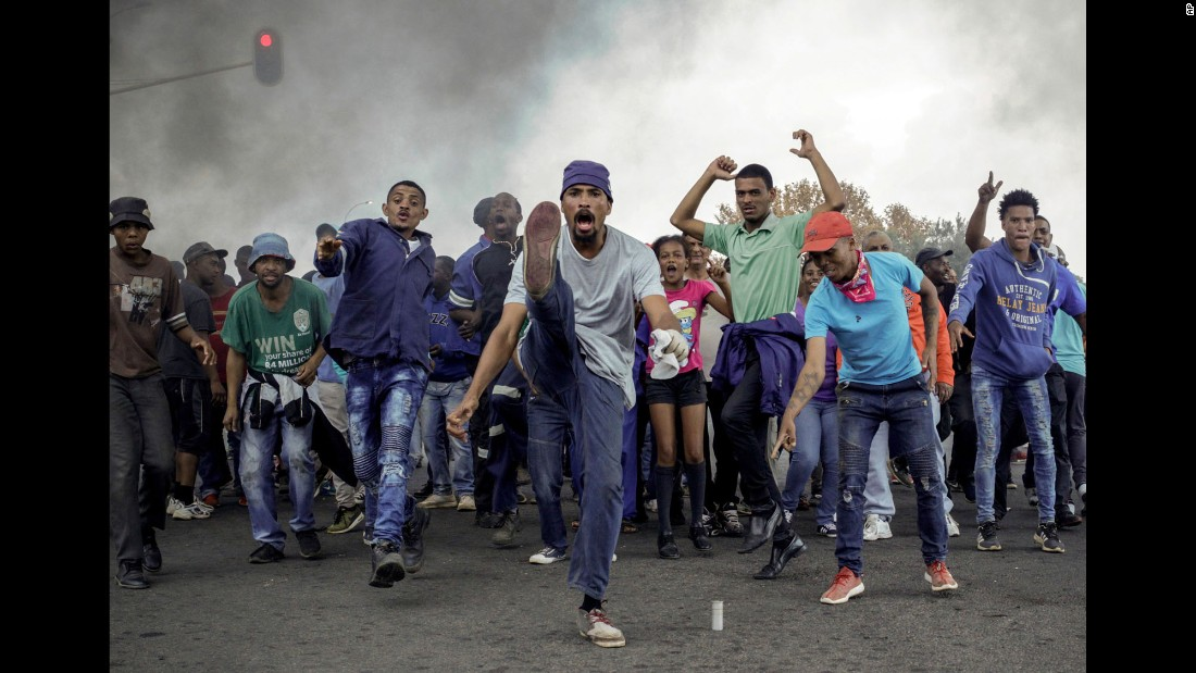 Protesters sing and chant in front of a burning barricade in Ennerdale, a Johannesburg suburb, on Tuesday, May 9. Violent protests over housing and government services erupted for a second day, with police firing rubber bullets at demonstrators who blocked roads and burned tires.