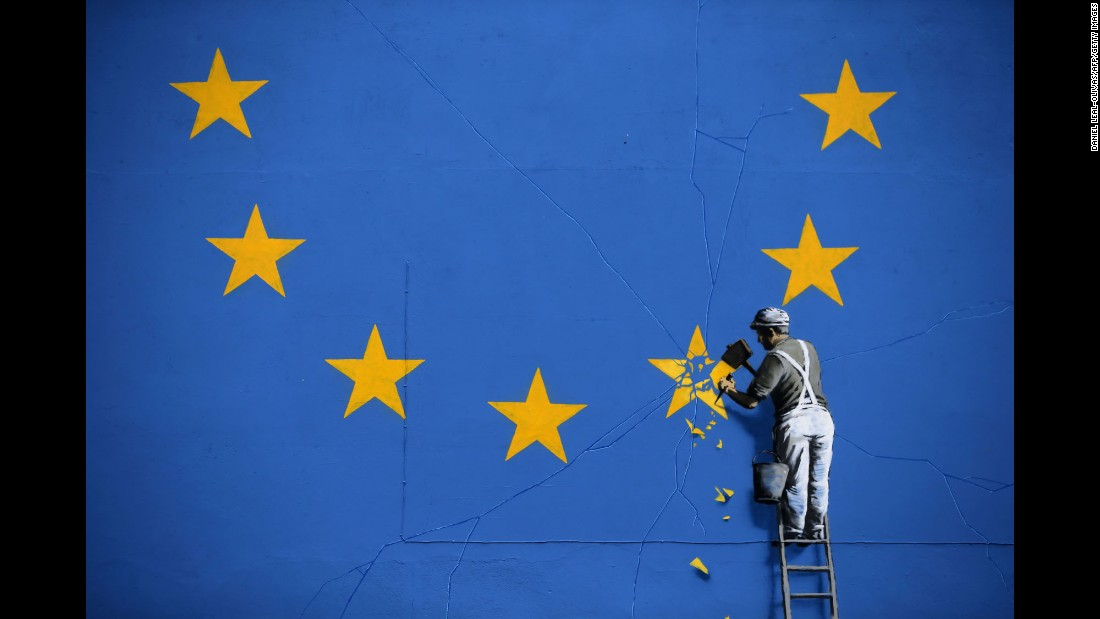 A mural in Dover, England -- recently painted by British graffiti artist Banksy -- depicts a worker chipping away at a European star on Monday, May 8.