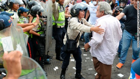 Opposition activists confront riot police during a protest against the government in Caracas on May 12, 2017. Daily clashes between demonstrators -who blame elected President Nicolas Maduro for an economic crisis that has caused food shortage- and security forces have left 38 people dead since April 1. Protesters demand early elections, accusing Maduro of repressing protesters and trying to install a dictatorship.  / AFP PHOTO / FEDERICO PARRA        (Photo credit should read FEDERICO PARRA/AFP/Getty Images)