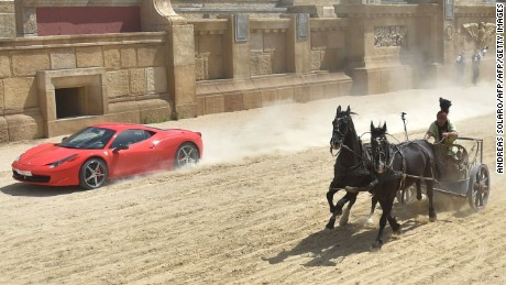 "TOPSHOT - Ferrari driver Fabio Barone and his Ferrari 458 Italia competes against a Roman chariot drawn by two horses on ""Ben Hur"" movie set at Cinecitta World amusement park on May 11, 2017 in Castel Romano near Rome.  / AFP PHOTO / Andreas SOLARO        (Photo credit should read ANDREAS SOLARO/AFP/Getty Images)"