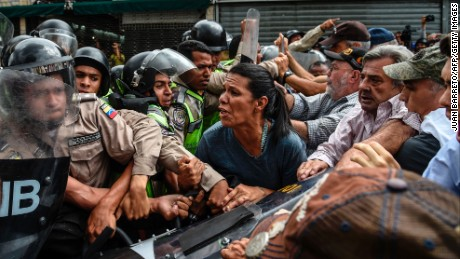 Opposition activists scuffle with riot police during a protest against the government in Caracas on May 12, 2017.