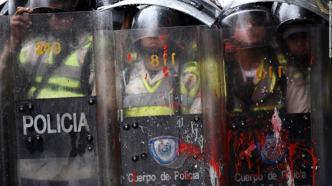 Shields of riot police are splattered with red paint during a protest in Caracas on May 12.