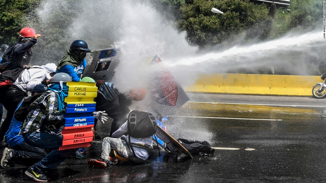 Riot police shoot a water cannon at opposition activists during a protest in Caracas on May 10.