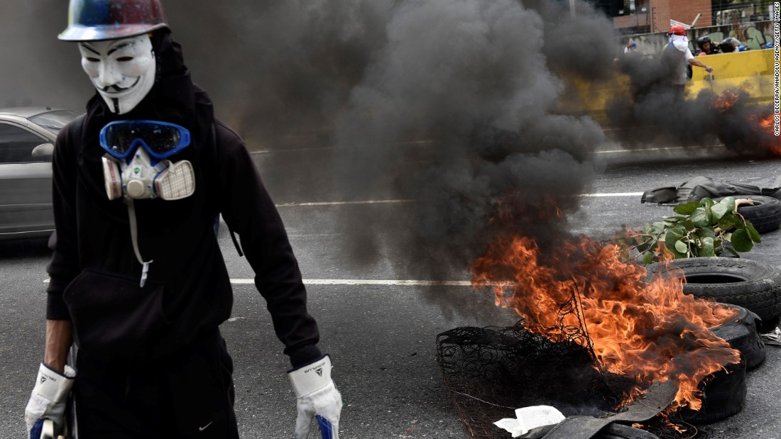 A masked protester sets debris on fire to block a highway in Caracas on Saturday, May 13.