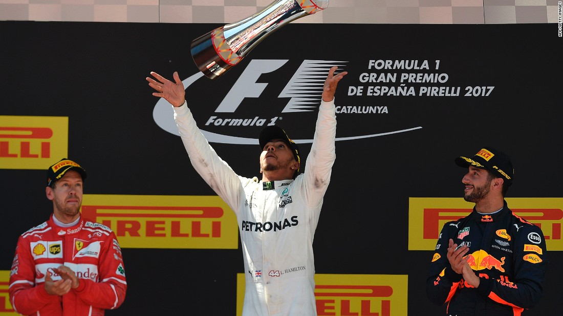 Hamilton celebrates on the podium flanked by second-placed Vettel and Red Bull's Daniel Ricciardo who finished third.