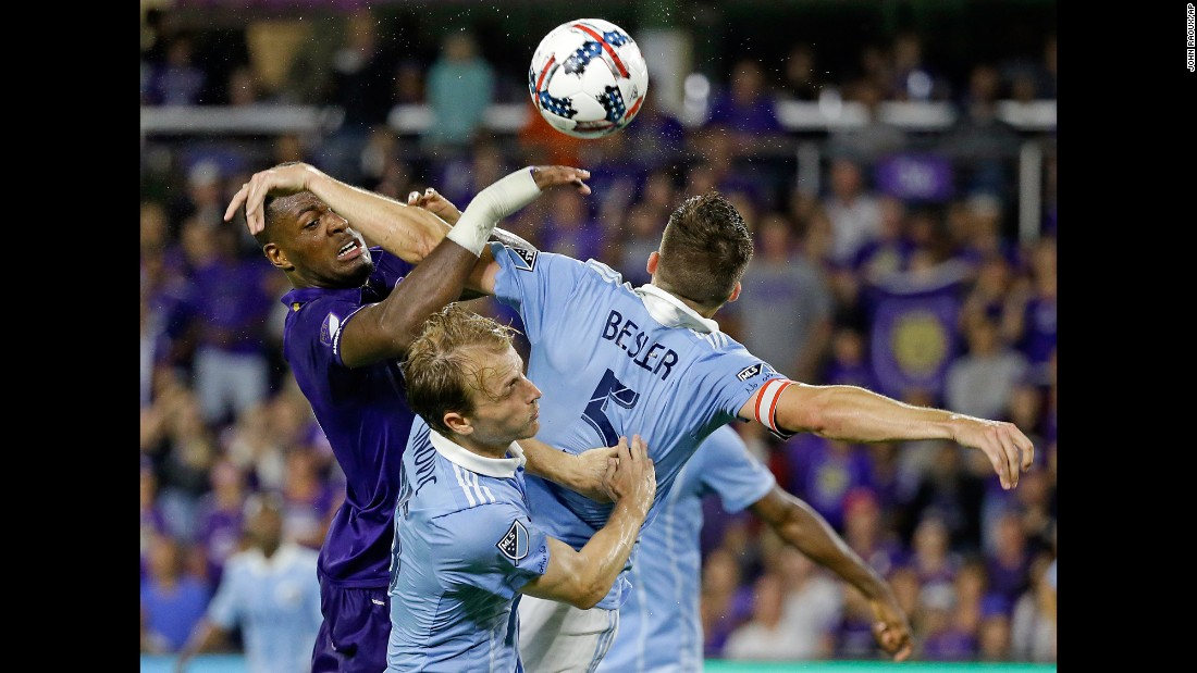 Orlando City's Cyle Larin, left, competes for a header with Sporting Kansas City's Seth Sinovic, center, and Matt Besler during a Major League Soccer match on Saturday, May 13.