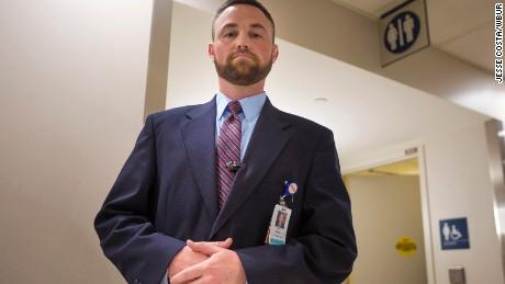 Ryan Curran of Massachusetts General Hospital in front of the bathrooms in the main lobby.