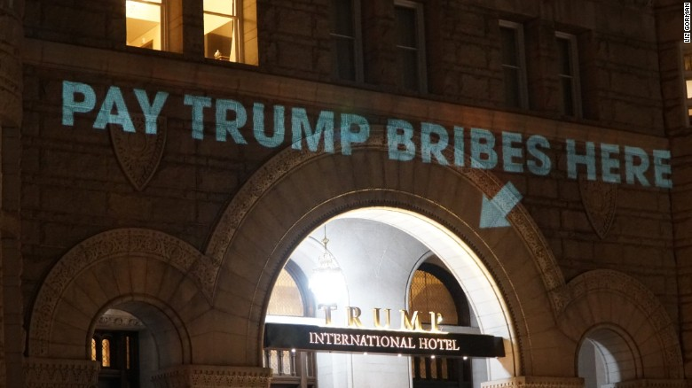 'Pay bribes here' projected onto Trump's hotel
