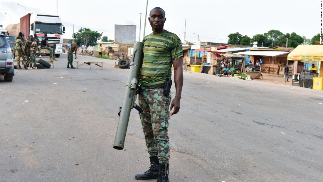 A mutinous soldier poses with a weapon in the streets of Ivory Coast's central second city Bouake during a four day uprising over unpaid bonus payments. <br /><br />Gunfire has been reported in several major cities after soldiers took to the streets.