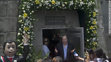 "The adoptive son of late Mexican comedian Mario Moreno ""Cantinflas"", Mario Moreno Ivanova (C), speaks at the tomb of his father at the Spanish Cementery in Mexico City, on August 12, 2011. Mexico Friday celebrates the 100th anniversary of Cantinflas' birth. AFP PHOTO/Yuri CORTEZ (Photo credit should read YURI CORTEZ/AFP/Getty Images)"