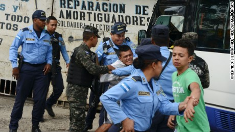 "Police officers try to hold a boy whose father, a bus driver, was killed by alleged gang members for refusing to pay them a ""war tax"", in Tegucigalpa on October 5, 2016. Honduras has one of the highest homicide rates in the world: more than six times the world average, according to the World Health Organization. Officials blame gangs and drug-traffickers.  / AFP / ORLANDO SIERRA        (Photo credit should read ORLANDO SIERRA/AFP/Getty Images)"