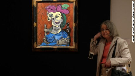 "Visitors walk around Pablo Picasso's depiction of Dora Maar in ""Femme assise, robe bleu"" during Christie's press preview of the 20th Century Week, in New York on May 5, 2017.                         Christie's and Sotheby's are currently holding their Spring Auction previews. / AFP PHOTO / Jewel SAMAD        (Photo credit should read JEWEL SAMAD/AFP/Getty Images)"
