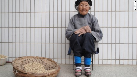 An elderly woman with bound feet sits by a basket in Yunnan, China