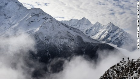 Climbers stand on a ridge over a valley leading north into the Khumbu region as they try to get a clear view of Mt. Everest, April 18, 2015.