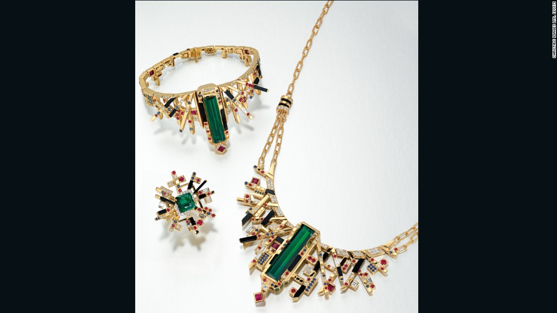 This jewelry set by Adrian Cheng comprises a neck chain, bracelet and ring centered on a striking green tourmaline, surround by onyx, rubies, sapphires and diamonds, mounted in gold.