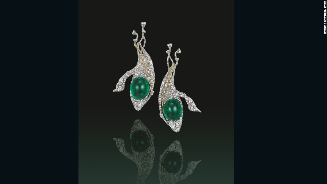 "This set of ear accessories by Cindy Chao is crafted in titanium around a pair of rare 29.49 carat and 26.81 carat cabochon emeralds, further ""suspended"" from a yellow diamond string."