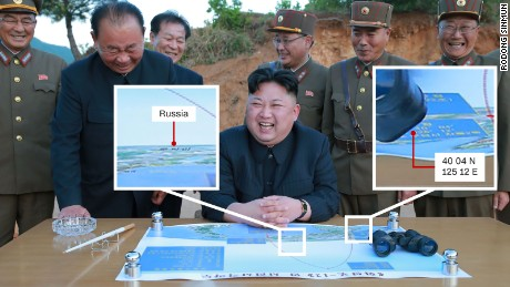 State media released images of Kim Jong Un with a map of the launch.