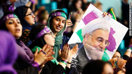 Supporters of Iranian President and presidential candidate Hassan Rouhani hold up his portrait during a campaign rally in the capital Tehran on May 13, 2017. / AFP PHOTO / ATTA KENARE        (Photo credit should read ATTA KENARE/AFP/Getty Images)