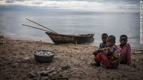 Children sit next to a bucket filled with fish on the shores of Tanganyika lake in Uvira on March 22, 2015. AFP PHOTO / FEDERICO SCOPPA        (Photo credit should read FEDERICO SCOPPA/AFP/Getty Images)