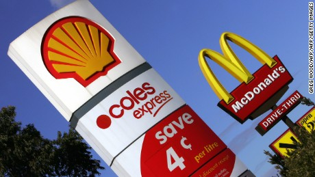 SYDNEY, AUSTRALIA:  Shell service station and McDonald's restaurant signs stand side by side near Sydney, 24 August 2005.  High demand for fuel in China and India, coupled with the current threat from a tropical depression that may develop into a Hurricane threatening the Gulf of Mexico, drove oil prices up over 66 USD a barrell, 24 August.  AFP PHOTO/Greg WOOD  (Photo credit should read GREG WOOD/AFP/Getty Images)