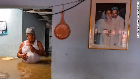 "A man wades at his flooded house in Cali, Colombia, on May 16, 2017, after heavy rains caused the overflowing of the Cauca river.  Colombia remains on ""alert"" due to heavy rains which, since March, have left 389 people killed, some 23.000 families and over a third of the country affected."