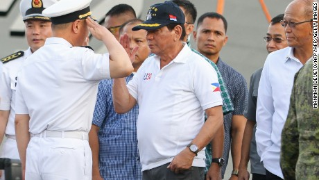 Philippine President Rodrigo Duterte (C) returns a salute from a Chinese naval officer (L) as Philippine Defence Secretary Delfin Lorenzana (R) looks on during Duterte's arrival to visit the guided missile frigate Changchun berthed at the Davao international port on May 1, 2017.  Philippine President Rodrigo Duterte on May 1 visited Chinese warships docked in his home town and raised the prospect of future joint exercises, highlighting fast-warming relations despite competing claims in the South China Sea. / AFP PHOTO / MANMAN DEJETO        (Photo credit should read MANMAN DEJETO/AFP/Getty Images)