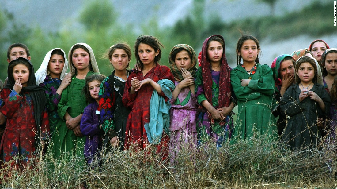 Afghan girls watch United Nations workers unload ballot kits ahead of the country's first democratic election in October 2004. Hamid Karzai was sworn in as President in December.