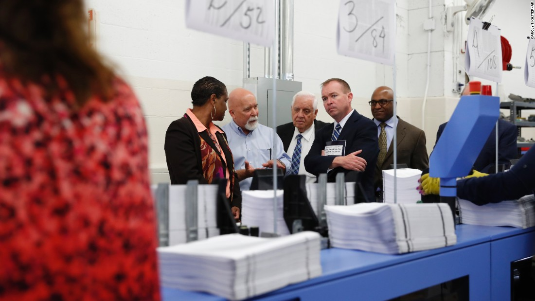 White House budget director Mick Mulvaney, second from right, inspects the production run of President Trump's printed budget as he visits a plant in Washington on Friday, May 19.