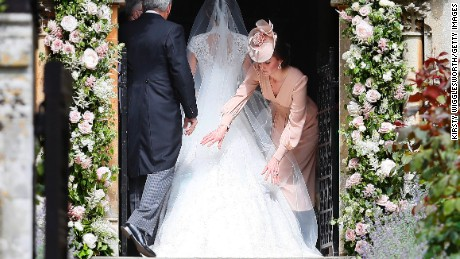 Catherine, Duchess of Cambridge, arranges the train of her sister Pippa Middleton's wedding dress.