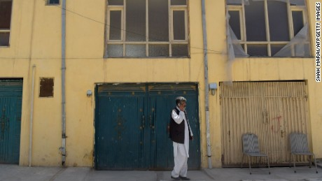 An Afghan man talks on a phone in front an international guest house that was attacked by gunmen in Kabul on Sunday.