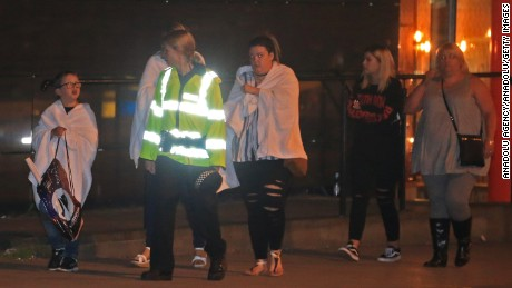 MANCHESTER, UNITED KINGDOM - MAY 23: A British police officer escorts walking casualties away from the Manchester Arena stadium in Manchester, United Kingdom on May 23, 2017.  A large explosion was reported earlier in the evening and British police confirmed that at least 19 killed and many other wounded at American singer Ariana Grande concert at Manchester Arena. Police said earlier the blast at the 21,000-seat arena shortly before 10.35 p.m. (2135GMT) local time was being investigated as a terror attack. (Photo by Lindsey Parnaby/Anadolu Agency/Getty Images)